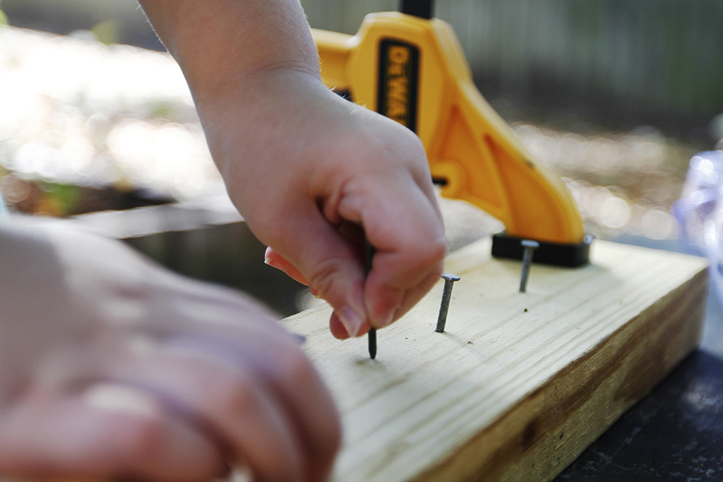 Child's hands placing nails into a board.